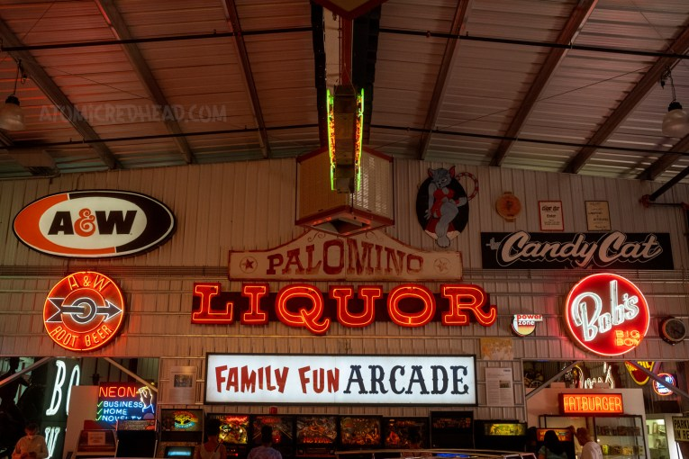 """A variety of signs hang on a wall, including a backlit plastic A & W sign, a painted sign reading """"Palomino"""" a red neon sign reading """"Liquor"""" a back lit plastic sign reading """"Family Fun Arcade"""" and a neon sign reading """"Bob's Big Boy"""""""