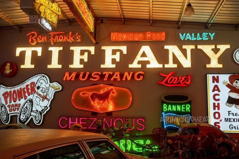 """A variety of lit signs hang on a wall, reading """"Ben Frank's"""" in red neon script, simple red neon letters reading """"Mexican Food,"""" blue neon letters reading """"Valley,"""" massive white bulb letters reading """"Tiffany,"""" back lit plastic sign for Pioneer Chicken, which is a chef sitting on a covered wagon. Red neon letters spell out """"Mustang"""" with a red neon horse below. A paint can sign reads """"Banner Paints"""""""