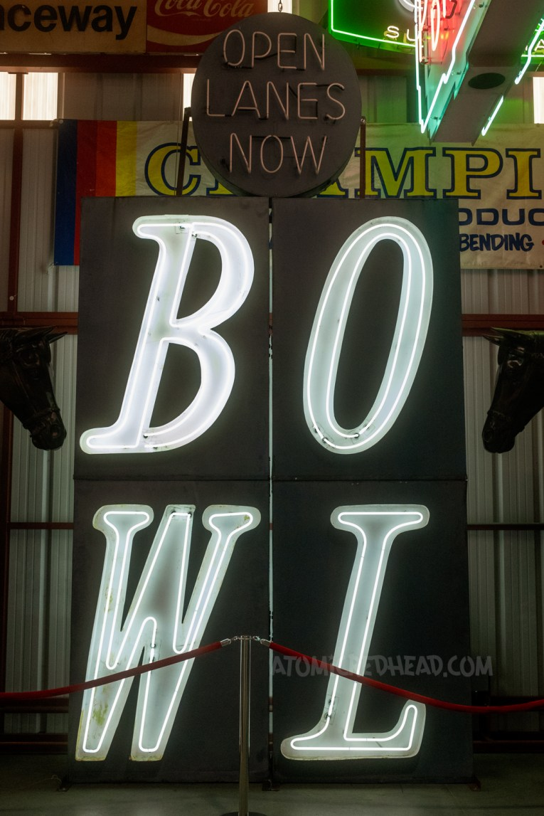 """A large black sign reading """"BOWL"""" in white neon."""