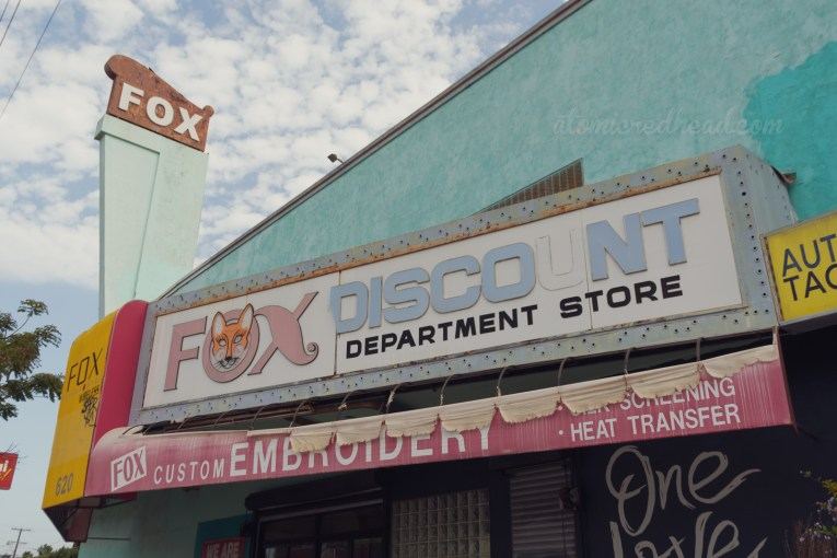 """A massive turquoise building features a tall spire at the top reads """"FOX"""" in white letters. Across the front is a faded backlit plastic marquee reading """"Fox Discount Department Store"""" the """"O"""" of """"Fox"""" features the face of a red fox. Below the marquee is a tattered red fabric sign advertising embroidery services."""