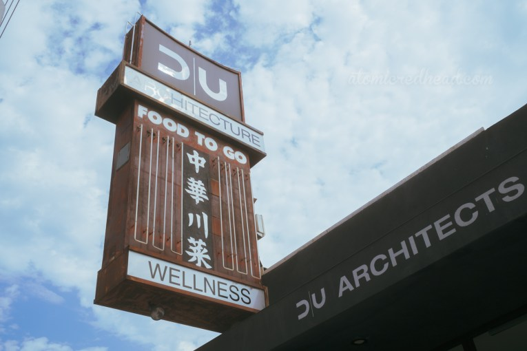 "A part backlit plastic, part neon sign reads ""DU Architects Wellness"""