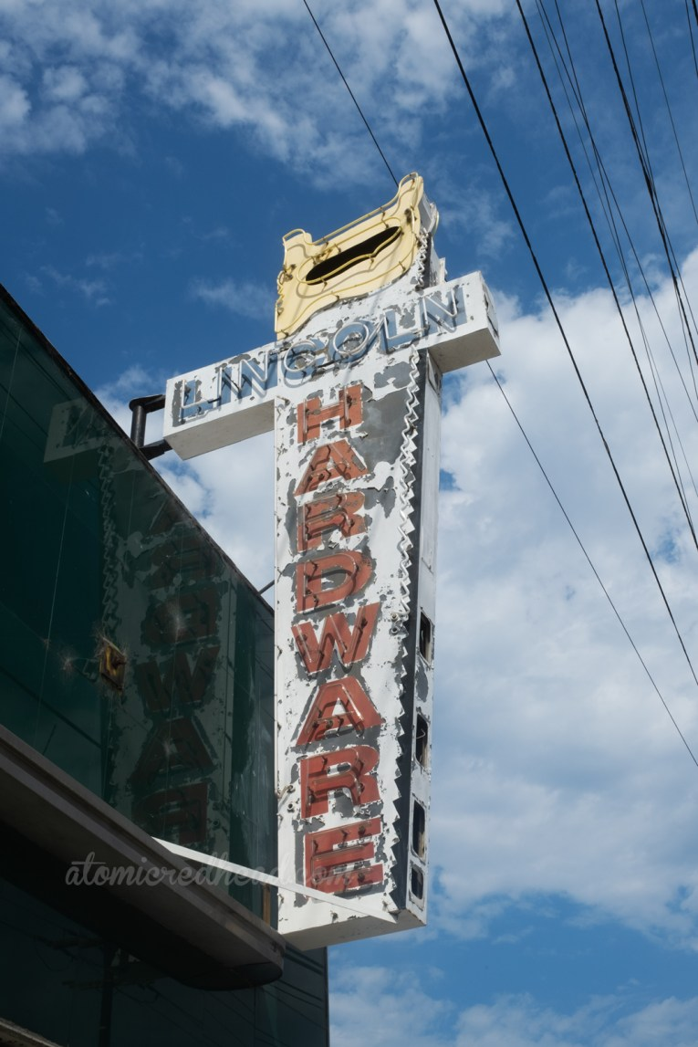 """A neon sign in the shape of a saw reads """"Lincoln Hardware"""""""