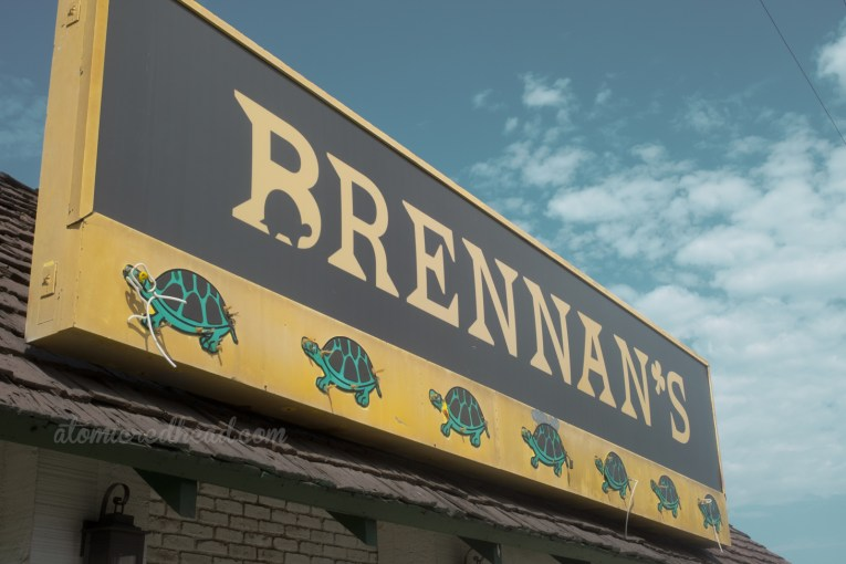"""A large backlit plastic sign reads """"Brennan's"""" and below six green turtles."""