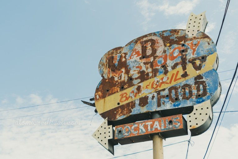 """A faded sign features a jumble of words, but """"Bar & Grill,"""" """"Food"""" and """"Cocktails"""" are visible."""
