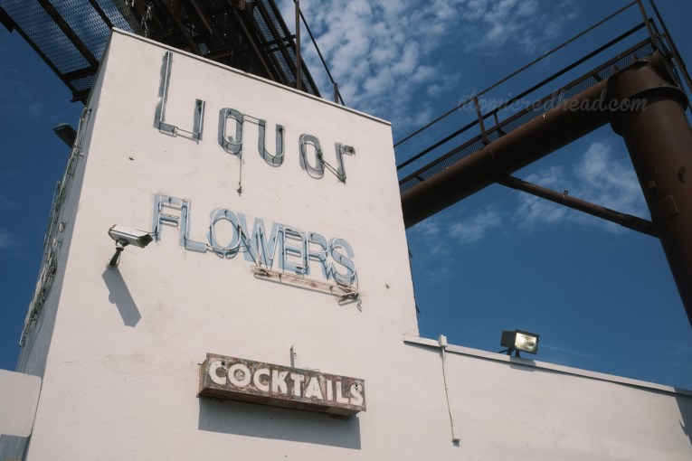 """A large white building reads """"Liquor,"""" """"Flowers,"""" and """"Cocktails"""" in neon."""