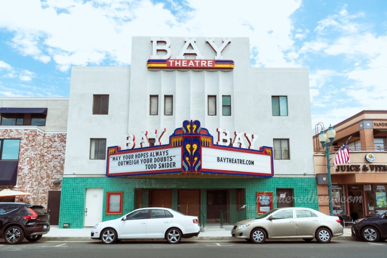 """A simple yet elegant cinema facade in the Streamline Modern style. Large letters read """"Bay Theatre"""" across the top, as well as across a marquee above the door. On the marquee reads """"May your hopes always outweigh your doubts"""" Todd Snider"""