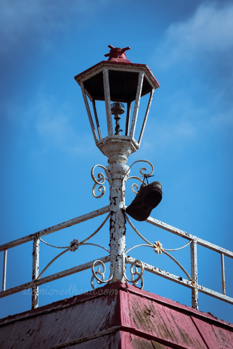 A broken out light fixture in the old lantern style, hands one lone shoe.