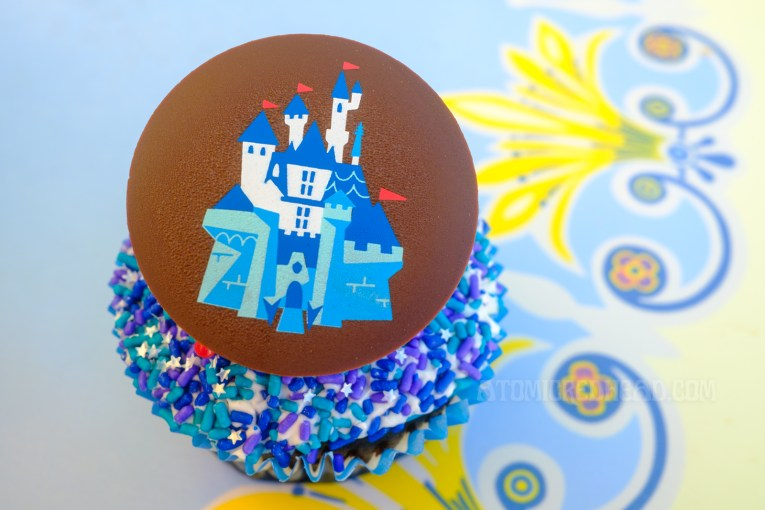A cupcake features a chocolate disk with a cartoon image of Sleeping Beauty Castle, under the disc are blue and white sprinkles.