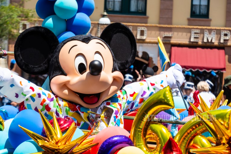 Mickey wears a colorful suit and waves at guests.