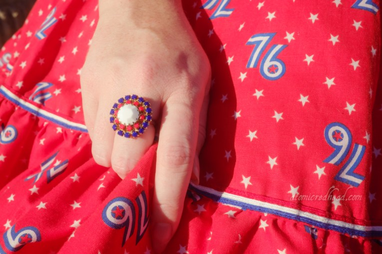 Close-up of my hand, wearing a ring made up of red, white, and blue stones.