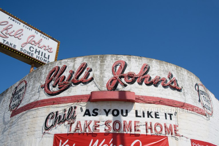 """Chili John's as it appears today, in the daylight. A white curved building with red painted script reading """"Chili John's"""" And text below reading """"Chili As You Like It Take Some Home"""""""