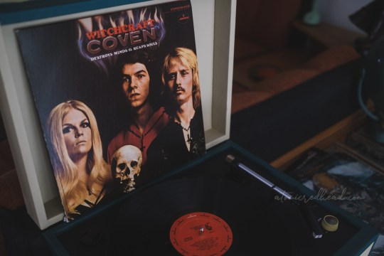 """The Coven Album """"Witchcraft"""" leans up against the open lid of a record player. The black vinyl record sits on the spindle. The cover features a woman with long blonde hair, and two men, one with dark hair, another with blonde hair and a mustache, in the middle is a human skull. Text across the top reads """"Witchcraft Destroys Minds & Reaps Souls Coven"""""""