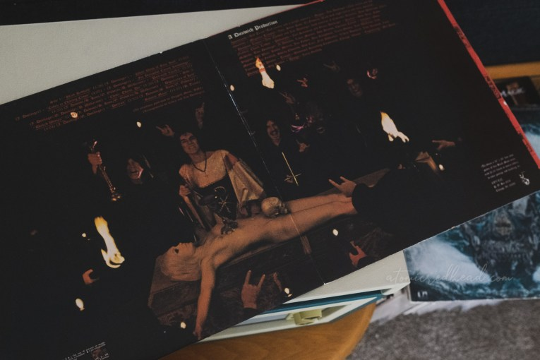Gatefold of the album, which features the blonde woman laid naked on the red alter, a skull covers her crotch. Men in black robes stand behind the alter, some have their hands raised with the sign of the horns.