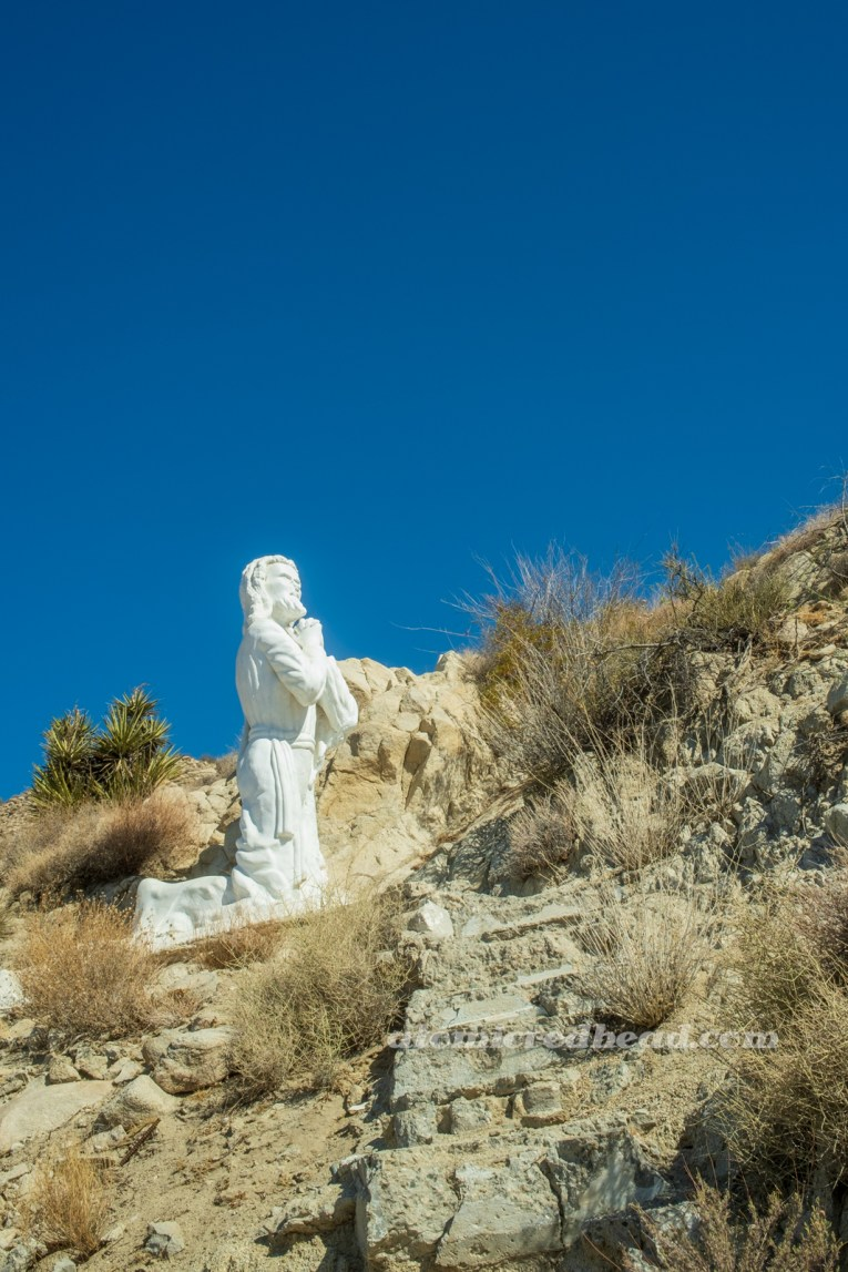 A white washed statue of Jesus kneels in prayer.