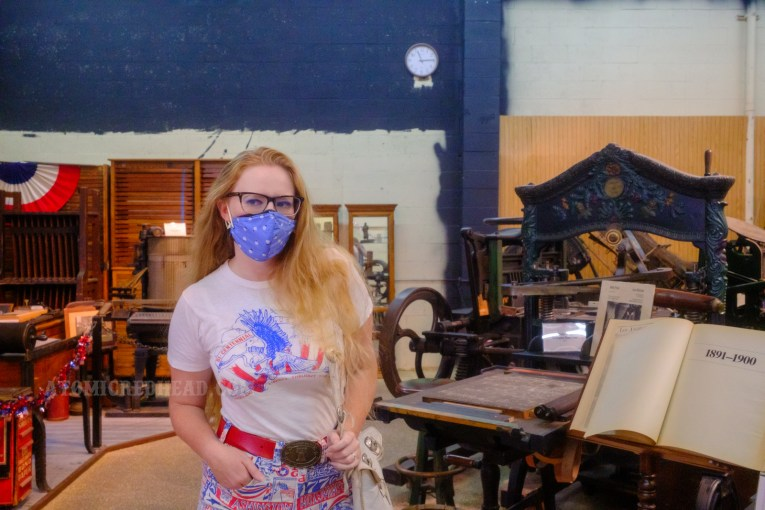 """Myself, wearing a white t-shirt with a bald eagle holding a bell with text reading """"Bi-Centennial 1776-1976 Proclaim Liberty thruout the Land"""" standing near a variety of antique printing presses"""