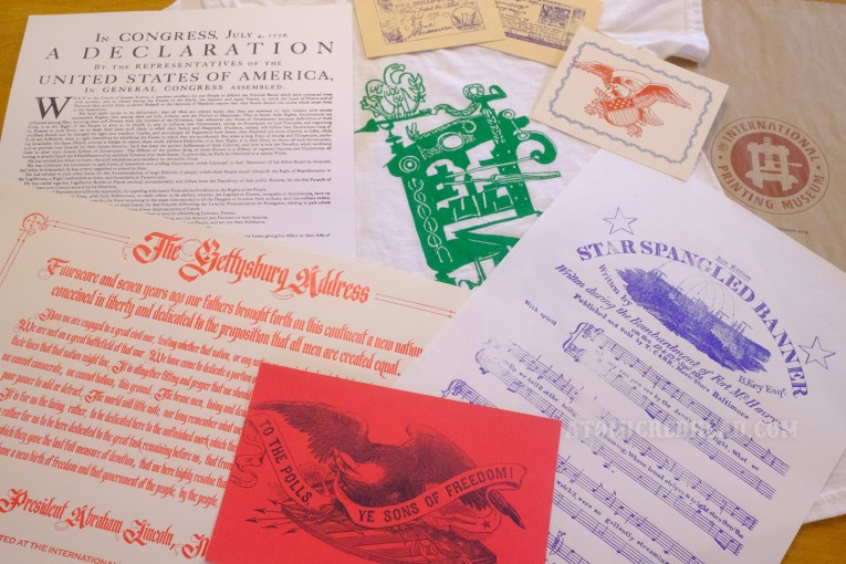 """Variety of paper goods made at the museum are scattered around a t-shirt with a printing press on it. Items include the Gettysburg Address, the music to """"The Star Spangled Banner,"""" the Declaration of Independence."""