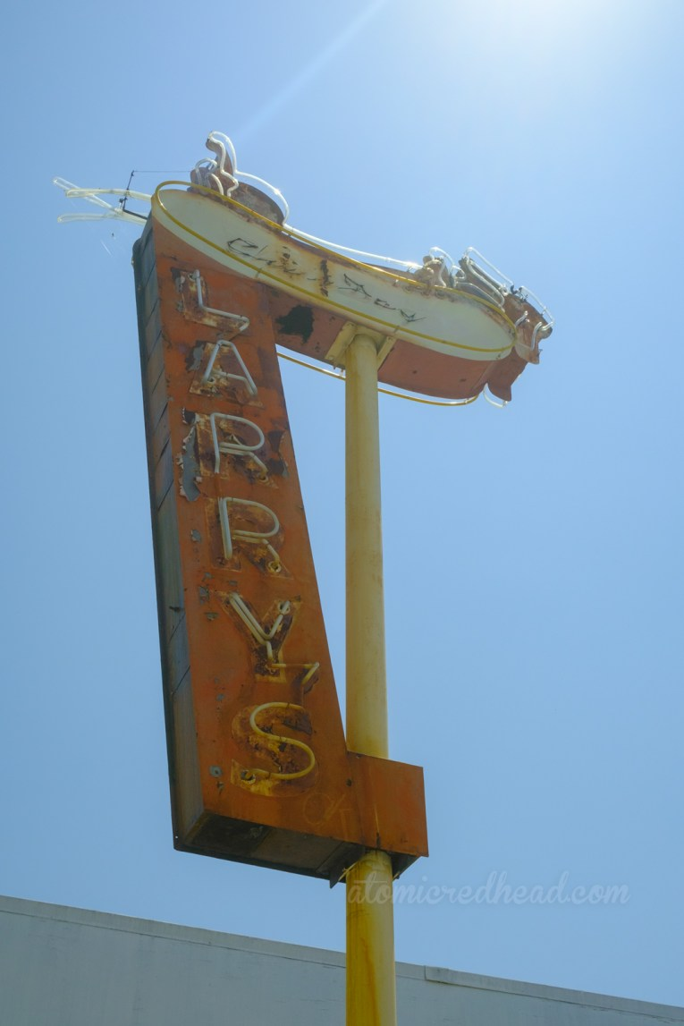 """Neon sign for Larry's Chili Dog, a dachshund sits in a bun, which across it reads """"Chili Dogs"""" below is a stretch of red reading """"Larry's"""""""