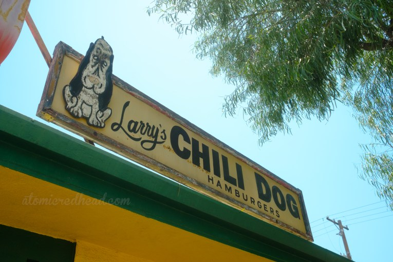 """A wooden sign with flaking paint features a cartoon dog and reads """"Larry's Chili Dog Hamburgers"""""""