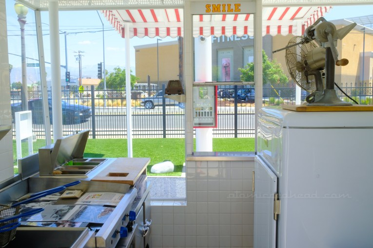 """Inside the replica, on the left is the food prep area and friers, the window to serve the customers is in the middle, with yellow letters above reading """"Smile"""" and to the left is a vintage white ice box."""