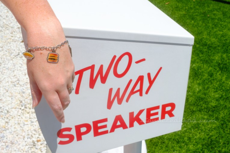 """Close-up of my charm bracelet, featuring charms of a burger and french fries, with my hand leaning on the white box that holds the speaker. Red letters reads """"Two-Way Speaker"""""""