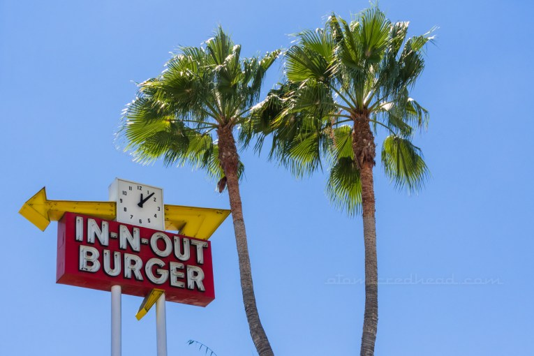Close-up of a vintage neon In-N-Out sign with a clock incorporated into the sign. Crossed palm trees stand to the right.
