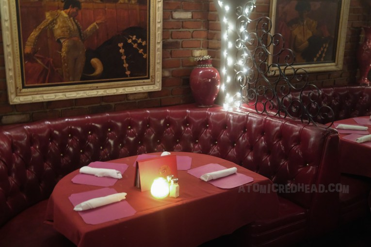 The same red leather booth inside Casa Vega, with a matador painting behind it.