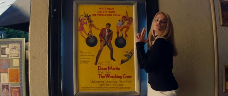Robbie as Tate poses next to the poster for The Wrecking Crew.