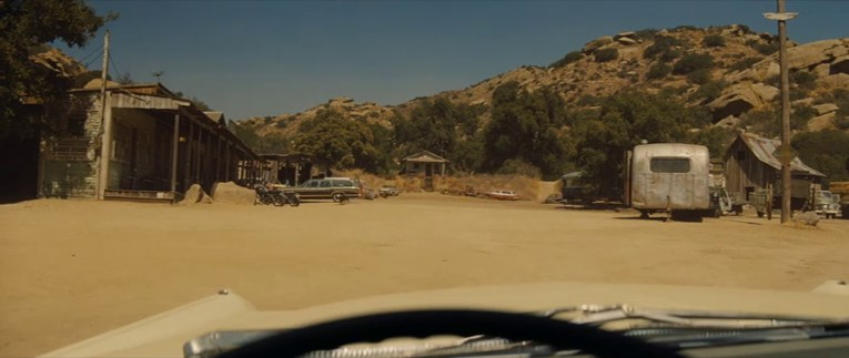 Screencap from Once Upon a Time...In Hollywood, looking through the windshield, a small house sits on a hill, with western style buildings on the left, and some cars scattered about.