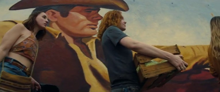 A massive mural of James Dean from his film Giant. He sits in a car dressed in cowboy attire, an old house visible in the distance, the hippie girls walk by carrying their dumpster finds.