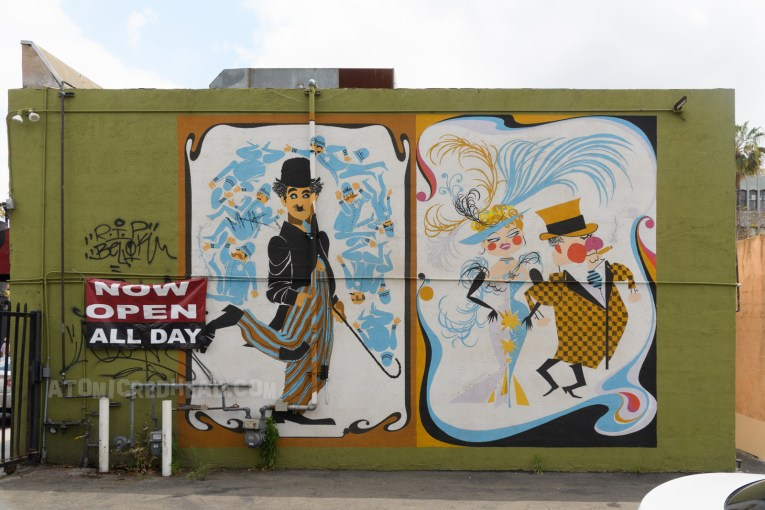 """Two murals of Elaine Hanelock's old Hollywood posters. One features Charlie Chaplin in his classic """"Tramp"""" outfit of black tails and a bowler hat. The other features A well dressed couple, Mae West and W.C. Fields."""