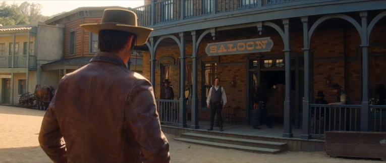 Screencap from Once Upon a Time...In Hollywood, Olyphant prepares for a gunfight in front of the saloon.