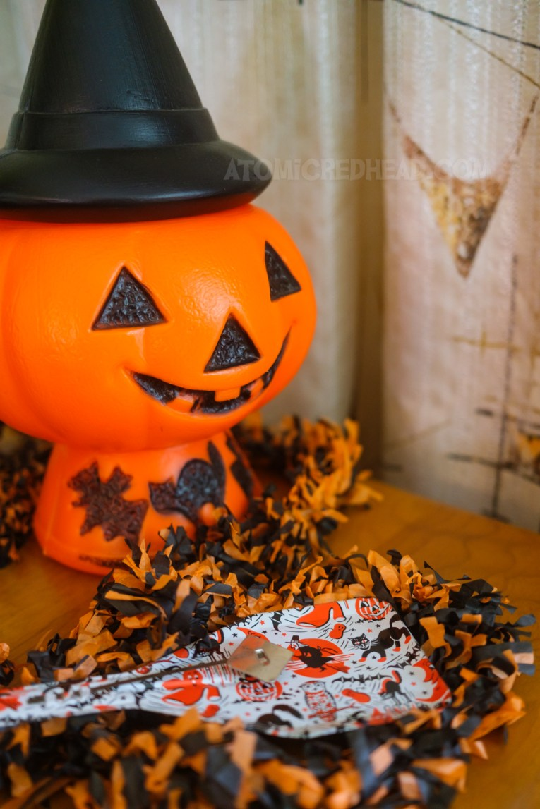 Close-up of a metal noisemaker with a spooky design featuring a witch, ghost, cat, and bat. In the background a blow mold Jack O'lantern with a with hat.