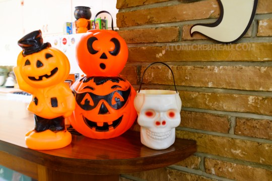 More blow mold sits on the bar by the kitchen, including a small blow mold scarecrow with a Jack O'lantern for a head, a small Jack O'lantern with a surprised look on his face, a larger Jack O'lantern wearing a mask over his eyes, and a white skull.