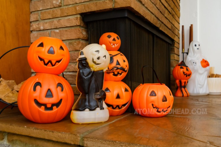 Blow mold sits near the fireplace, various Jack O'lanterns are stacked atop each other, and a small witch holds a pumpkin.