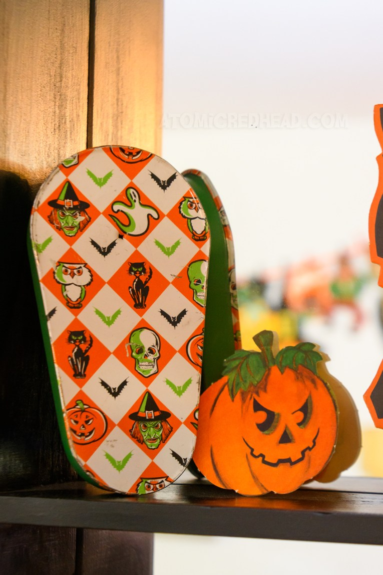 A vintage noisemaker featuring a harlequin pattern of orange and white with spooky figures inside the diamonds, such as a skull, witch, black cat, and bats.