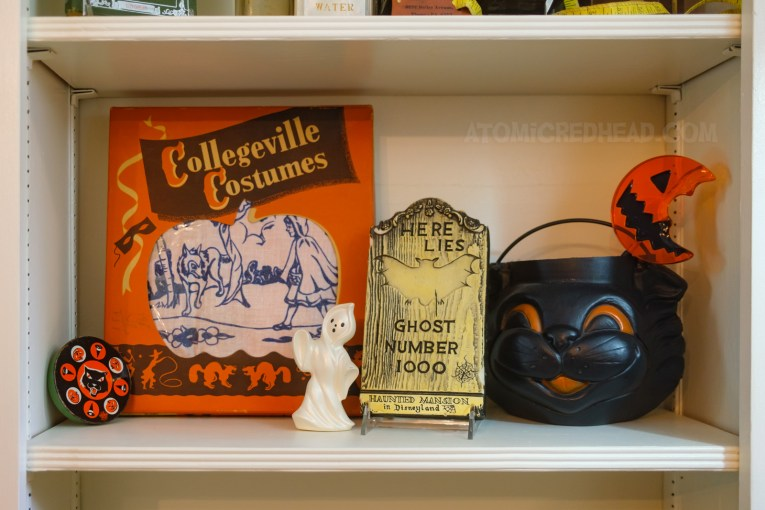 """Close-up of a bookshelf, with a costume box for a Little Red Riding Hood costume, a vintage noise maker featuring a black cat, a small ceramic ghost, a tombstone reading """"Here Lies Ghost Number 1000 Disneyland Haunted Mansion"""" and a black cat blow mold trick or treat bucket, which inside sits the half eaten lollipop from the film Trick 'r Treat."""