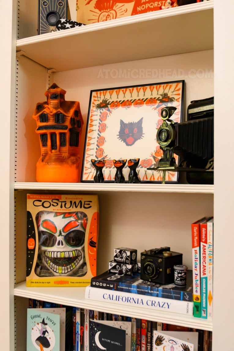 Two of the bookshelves, the upper one sits a blow mold haunted house, a framed vintage napkin with Jack O'lanterns, witches, and brooms, in front sits three ceramic black cats. Below is a box holding a skeleton costume, and some books.