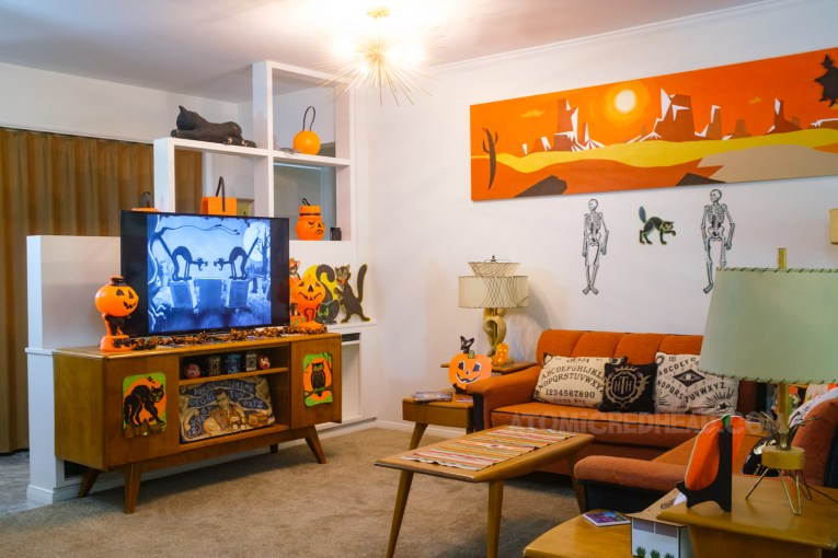 Overall view of our living room, with the television, couches, and coffee table, above is a long painting of a desert landscape.