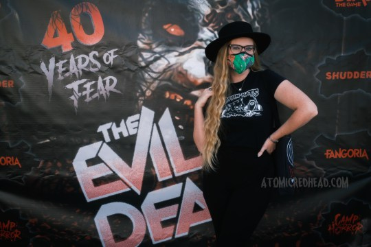 """Myself, wearing a black cowboy hat, a Koffin Kats tee, and black pants, standing in front of a large banner reading """"40 Years of Fear The Evil Dead"""" featuring the Deadite version of Cheryl."""