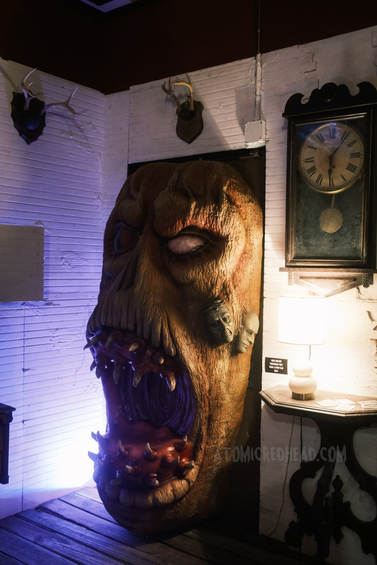 A massive Deadite face pushes its way through a doorway, an antique clock hangs on the wall to the right.