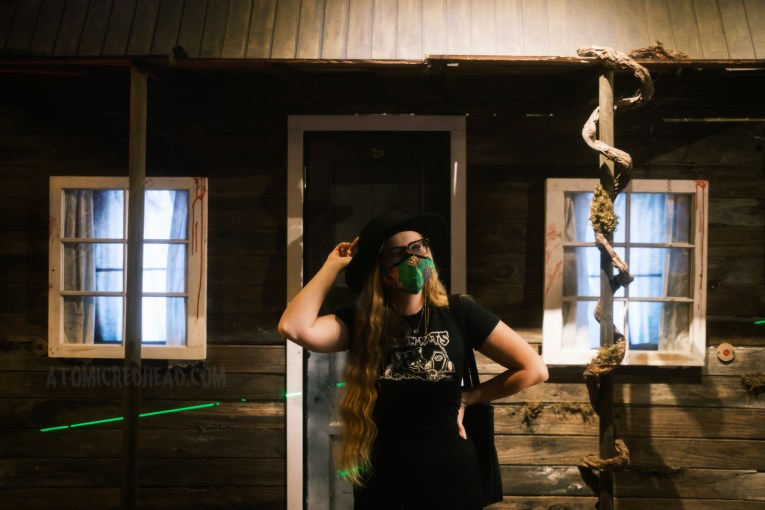 Myself, wearing a black cowboy hat, Evil Dead 2 themed mask, a Koffin Kats tee, and black pants, standing in front of a mock up of the cabin seen in the films.