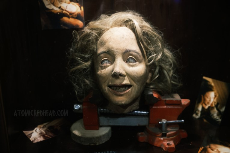 Linda's screen used severed head sits in a vice.
