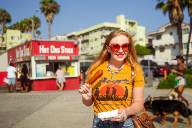 Myself, wearing a yellow shirt featuring the band The Doors, standing in front of Hot Dog on a Stick holding a corndog.