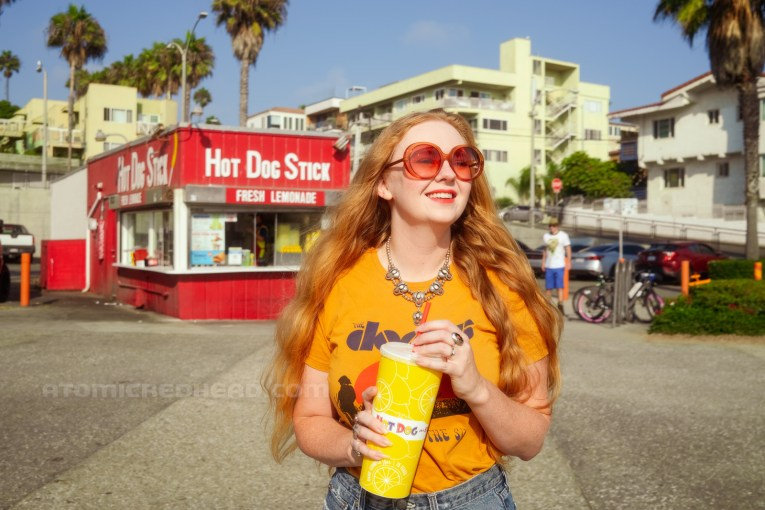 Myself, wearing a yellow shirt featuring the band The Doors, standing in front of Hot Dog on a Stick holding a cup of lemonade.