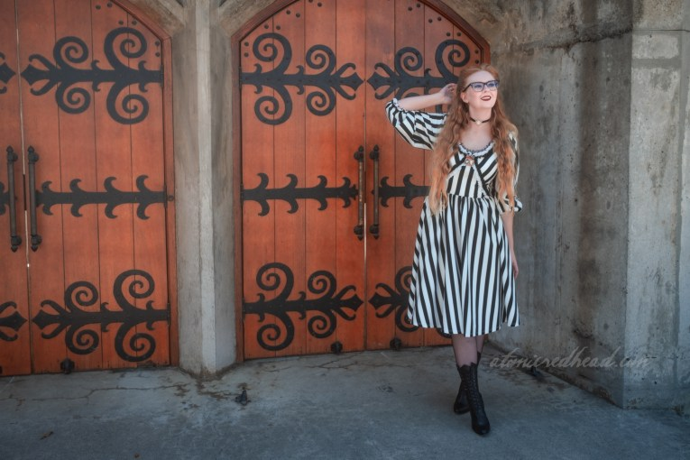 Myself, wearing a black and white stripe dress, a pin featuring the Headless Horseman, Ichabod and Katrina sits at the center of the neckline, a black choker with a rhinestone star charm in the center, and black lace up boots, standing in front of a large wooden door with black, curling wrought iron details.