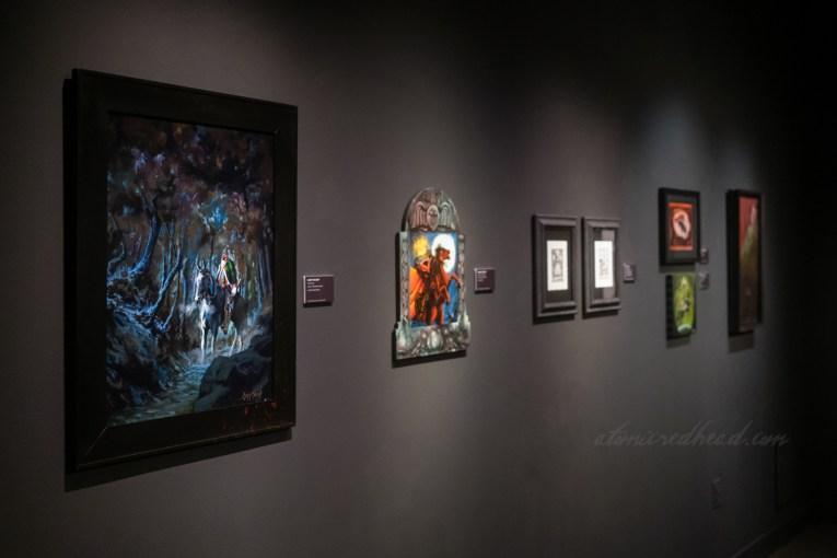 Art portion, various art featuring the Headless Horseman is hung on black walls