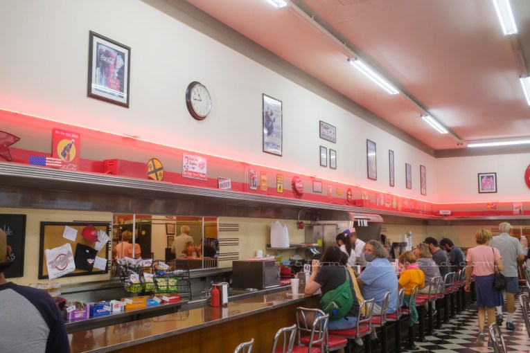 Angled view of the lunch counter, which is dark wood formica, with chrome seats with red upholstery. Red neon runs across the wall above the back work counter. Various Coca-Cola advertisements are framed on the cream wall.