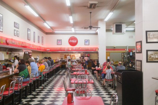 Overall view of the lunch counter. The counter runs along the left side, sweeping across the back. Black and white checkered floor allows for table seating with red formica topped tables and red and chrome chairs. A red stripe runs across the wall with red neon above. Framed Coca-Cola ads line the upper, cream portion of the wall, a large circular Coca-Cola sign sits on the back wall.