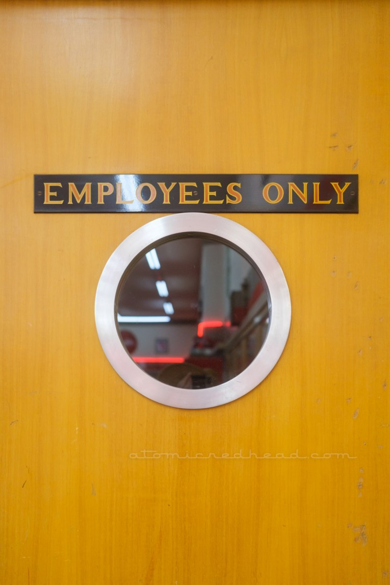 """A wood door features a porthole style window with a hand painted sign above reading """"Employees Only"""""""