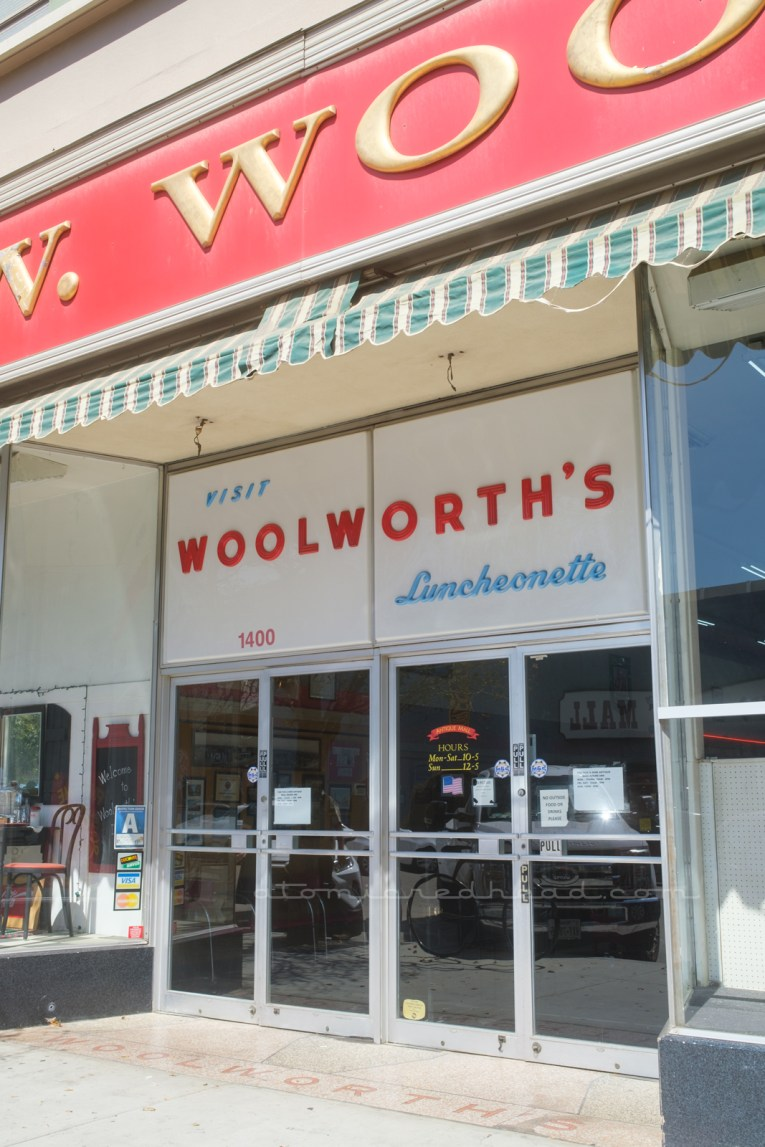 """Under a red and gold sign read """"F.W. Woolworth's"""" is a large white plastic sign sits above the doorway to the antique mall. Small blue letters read """"Visit"""" followed by large red letters reading """"Woolorth's"""" and then below in smaller blue script reads """"Luncheonette"""""""